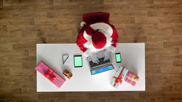 Santa Claus working at office on laptop, smartphone and tablet with chromakey Footage