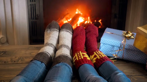 Slow motion footage of two people wearing knitted woolen socks resting by the Footage