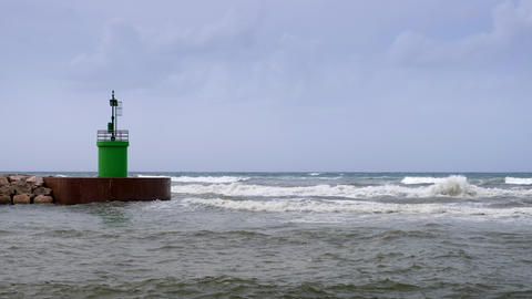 Waves hitting green lighthouse tower of a harbor entrance Footage