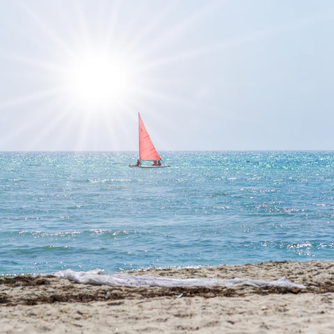 boat with red sails swims away by the sea Photo