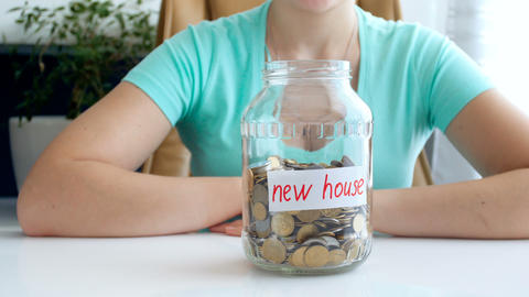 4k conceptual video of young woman collecting and saving money for new house Live Action