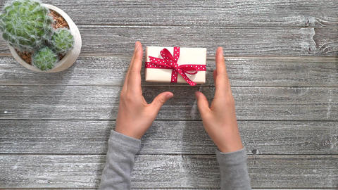 Woman tying a bow on a present box Footage