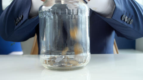 4k video of young businessman in suit throwing heap of coins in glass jar Footage