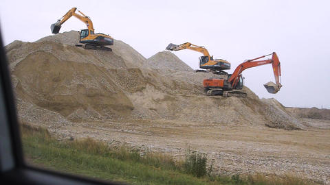 Excavators on unpaved embankments develop a quarry along a roadside View from a Live Action