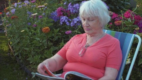 Senior woman reading magazine in garden with flowers outdoor Footage