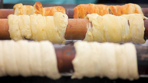 Delicious trdelnik browning on wooden sticks at high temperature, Czech cuisine Footage