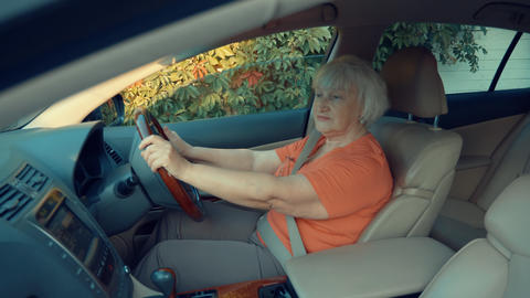 Senior woman listening music and holding steering wheel in car Footage