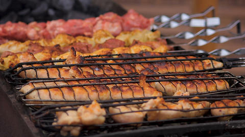 Large amount of unhealthy fatty junk food cooking on grills at street festival Live Action