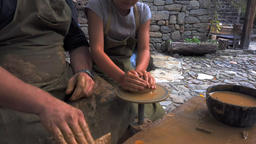 Potter's hands and the child's hand in clay over a potter's wheel. A master Footage
