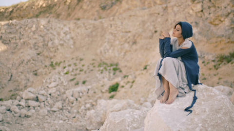 sad young woman sits on a rock in the background of the mountains Footage