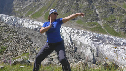 A woman is doing oriental exercises overlooking the beautiful mountains. Healthy Footage