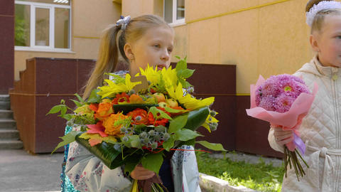 Portraits pupil girls with bouquet flowers, back to school concept Footage