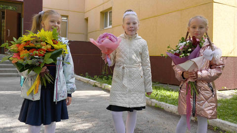 Happy schoolgirls with flowers smiling and looking to camera. Back to school Footage