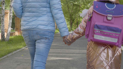 Mother and pupil of primary school walk to first class. Back to school concept Live Action