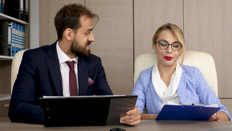 Two business partners discussing and analyzing strategy business on clipboards Footage