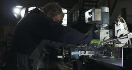 Automotive Shop Worker Pulls Down the Lever of a Metal Cutting Saw Footage