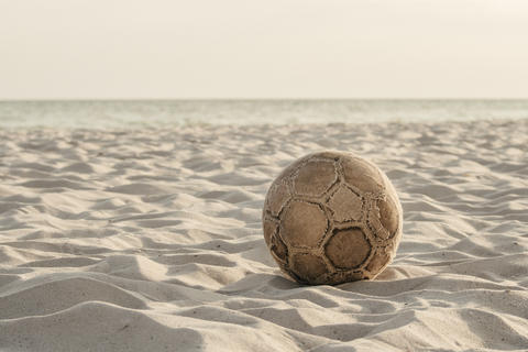 Old worn soccer ball on the beach フォト