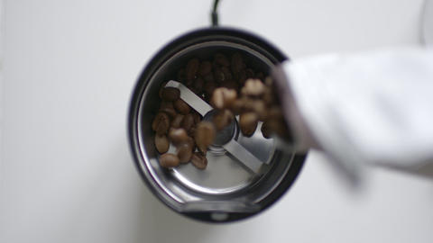 Roasted coffee beans poured into a coffee grinder Live Action