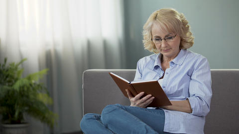 Middle-aged housewife sitting on sofa and reading interesting book, hobby Footage