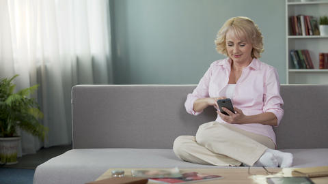 Gorgeous middle age woman viewing photos in social media on cellphone, app Footage
