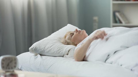 Healthy sleep. Blond senior woman sleeping in bed on orthopedic mattress Live Action