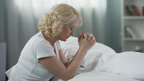 Senior female sitting on the floor near bed and praying, religion and belief Live Action