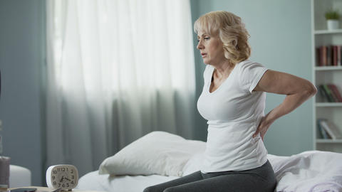 Blond mature lady sitting on bed and touching her back, radiculitis and pain Live Action