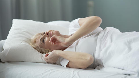 Happy senior female lying in bed and thinking about perfect date, sexual health Footage