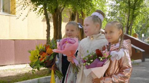 Cheerful schoolgirls with flowers talking and standing near school together GIF