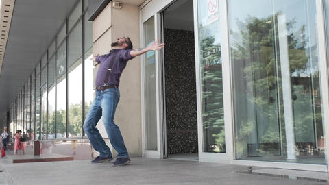 A man jumps out of the buliding entrance and starts to dance silly Footage