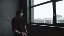 Young Man Dancing Beside Stairwell Window and Wall Footage
