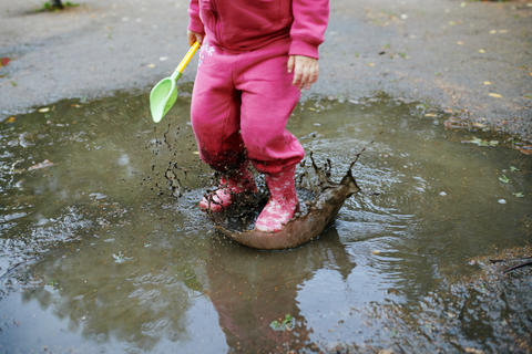 Child jumps in a dirty puddle Photo
