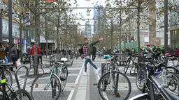 Street Dancer Performing Between Bicycles and People on Pedestrian Street Live Action