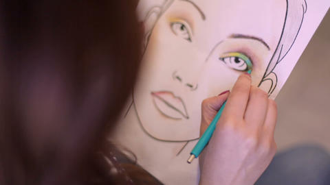 Face chart: Woman make-up artist learns to apply make-up using the face map Footage
