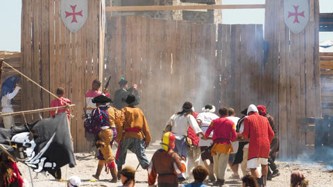 Theatrical staging of the attack of medieval pirates on a wooden fort Shots and Live Action