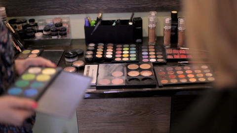 Professional cosmetics. Make-up artist selects cosmetics for the client in the Live Action