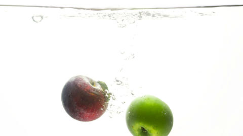 Closeup slow motion video of fresh green and red apple falling in cold water Footage