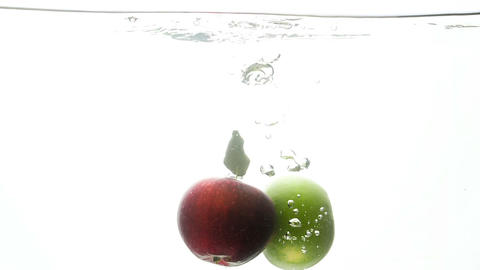 Slow motion video of two fresh red and green apples falling and splashing in Footage