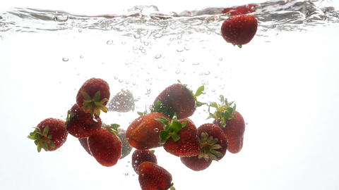 Closeup slow motion footage of lots of raspberries falling and splashing in Footage