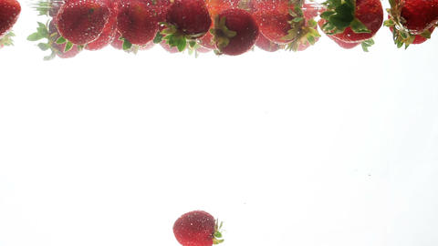 Closeup footage of red ripe raspberries slowly floating in water against white Footage