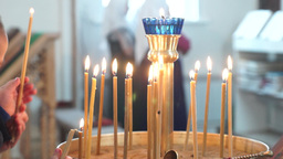 Woman With A Child Set Fire And Put A Candle During The Liturgy In An Orthodox C stock footage