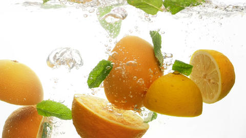 Closeup slow motion footage of juicy and ripe citrus fruits falling into water Footage