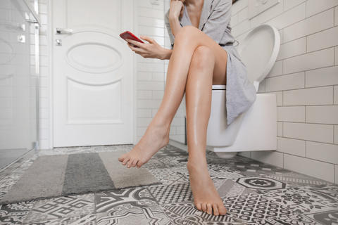 Woman sitting on the toilet with phone Photo
