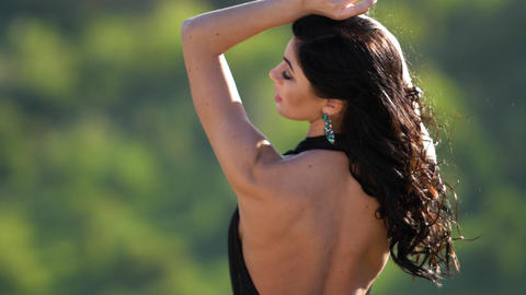 Luxurious sexy woman is standing with her back to the camera Hair is fluttering Footage