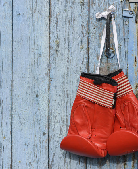 red leather boxing gloves hanging on an old blue wooden wall Fotografía