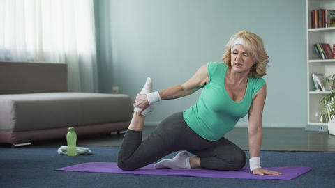 Tired mature woman doing yoga exercises, stretching legs. Healthy lifestyle Live Action