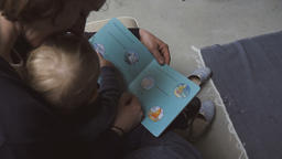 Mother Reading a Book to Baby Girl Live Action