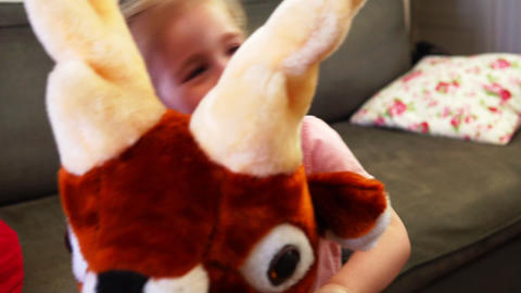 A happy baby rides a toy deer in slow motion Footage