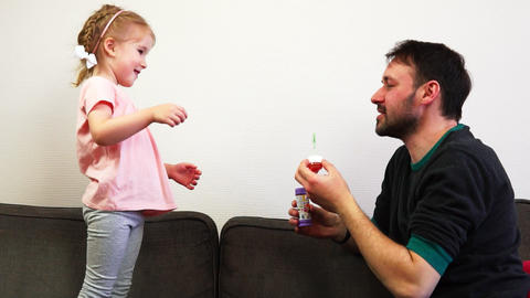 A father blows a soap bubble and his daughter pops it in slow motion Archivo