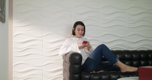 Young Hispanic Girl Messaging With Cell Phone On Sofa Footage